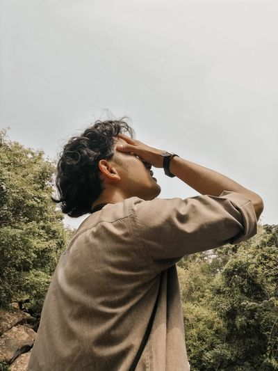Side view of man covering his face against sky