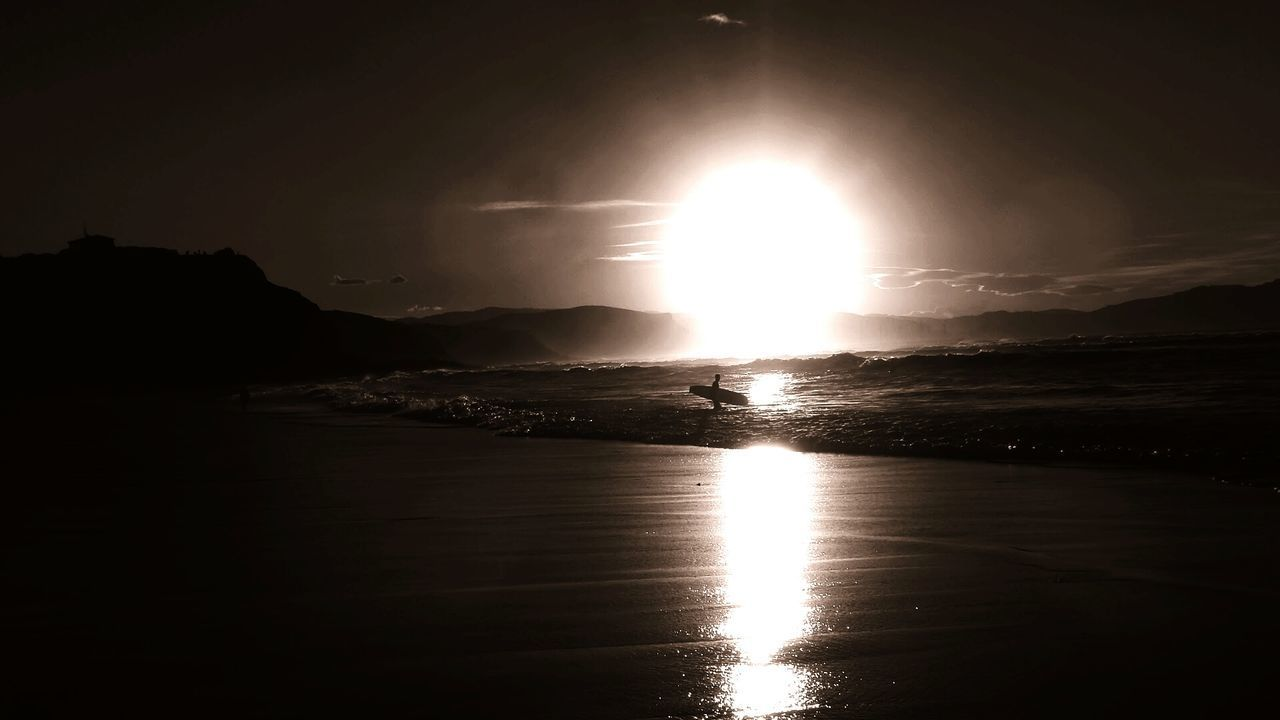Silhouette Surfer Carrying Surfboard In Sea Against Sun