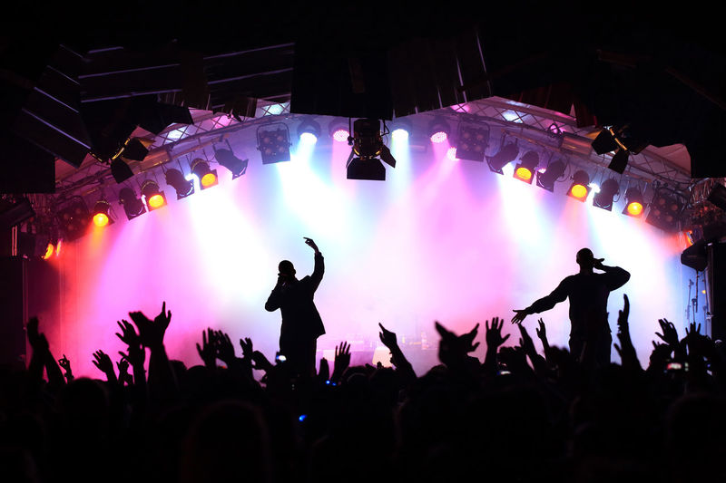 Singers performing on stage by people during concert