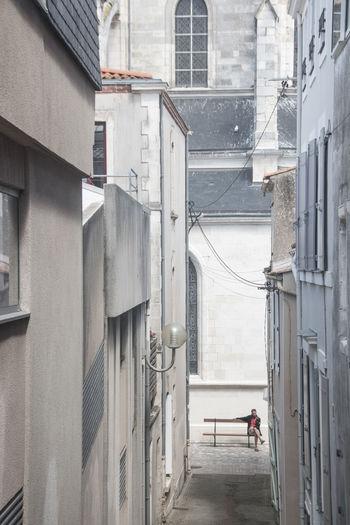 People walking on alley amidst buildings in city