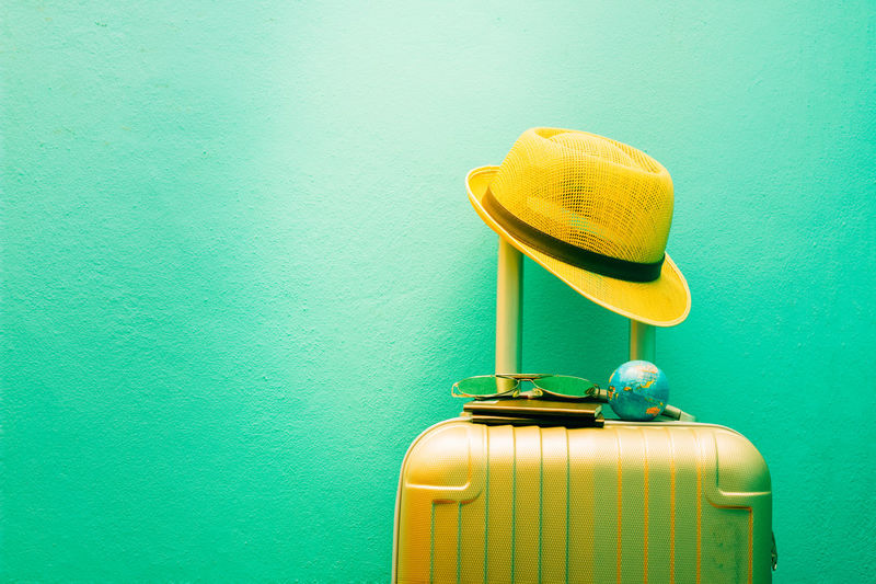 Glasses Passport Travel Arrangements Adventure Blue Built Structure Colored Background Container Green Color Hat Luggage Retro Styled Studio Shot Suitcase Sunglasses Travel Destinations Turquoise Colored Wall Wall - Building Feature Yellow
