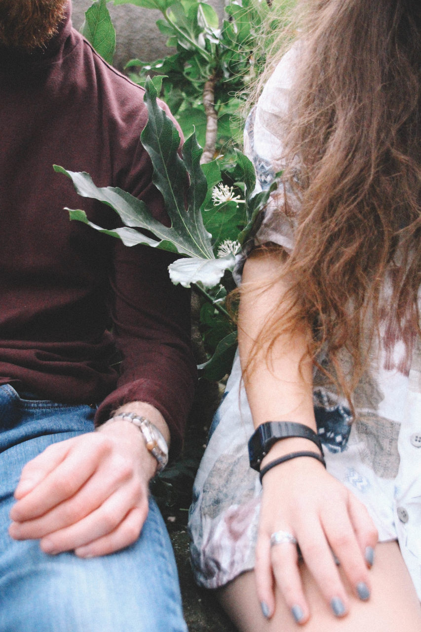Midsection Of Couple Sitting By Plants
