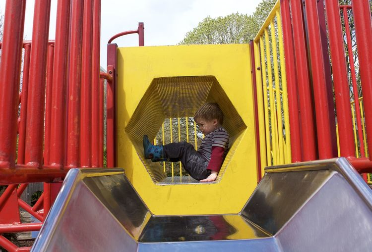 Side View Full Length Of Playful Boy In Play Equipment At Park