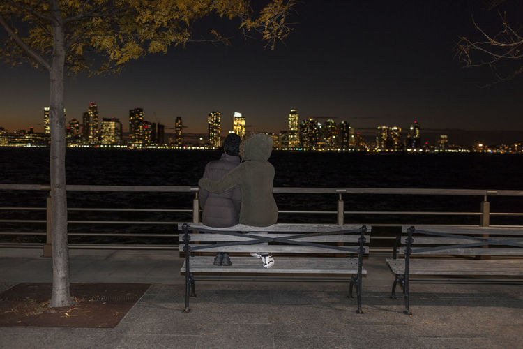 Rear view of woman sitting on bench in city at night