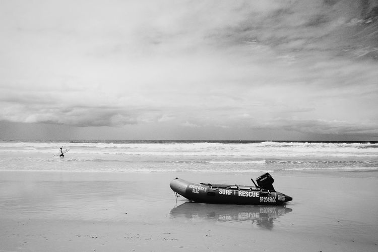 Lifeboat on beach against cloudy sky