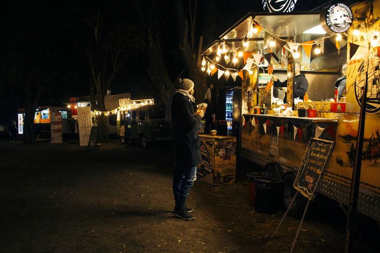 Man standing by illuminated street market at night