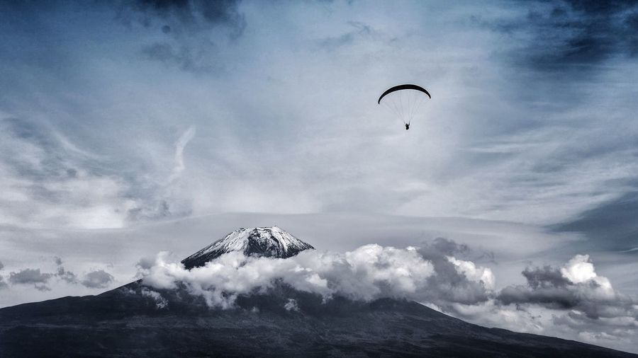 Low Angle View Of Person Paragliding Over Mountain Against Cloudy Sky