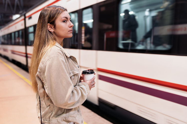 Young woman standing by train at railroad station