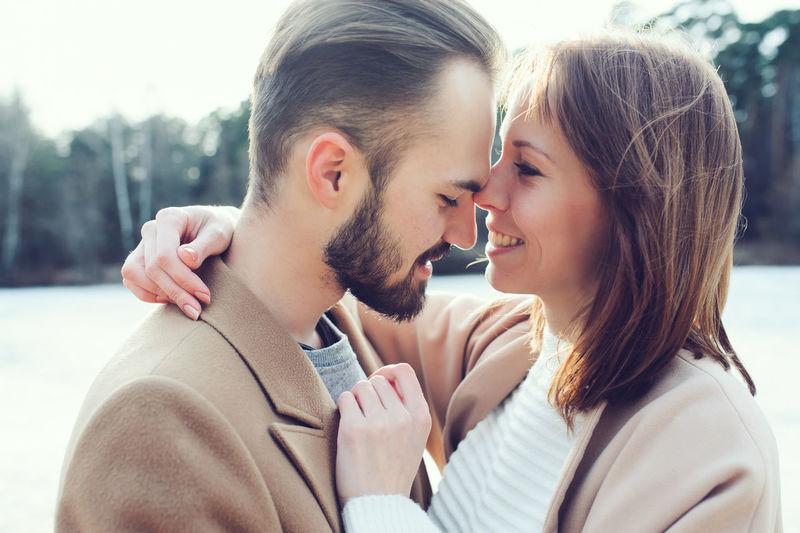 Smiling Young Couple Romancing At Riverbank