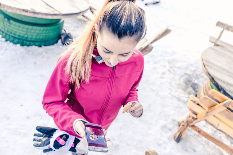 High angle view of teenage girl using mobile phone while standing on snow field