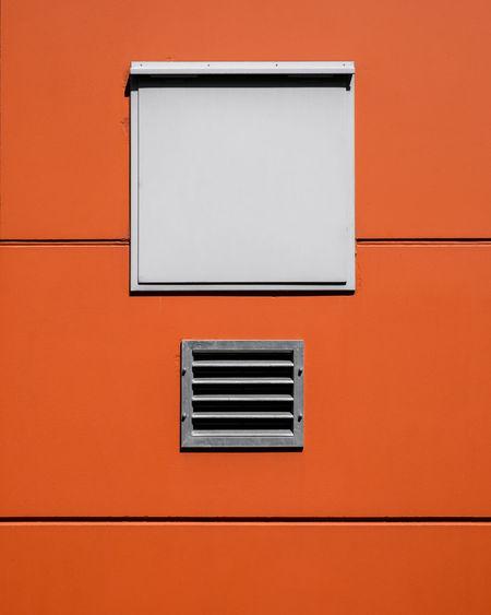 Low angle view of window on orange wall