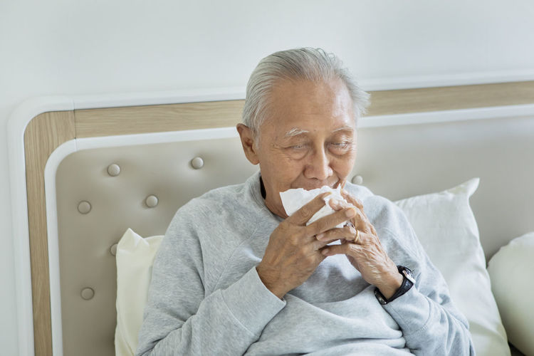 Man holding tissue paper while sitting on bed at home