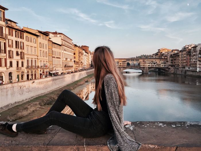 Side view of woman sitting in city against sky