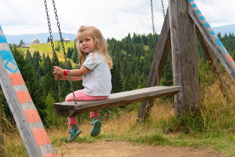 Full length of girl on swing in playground