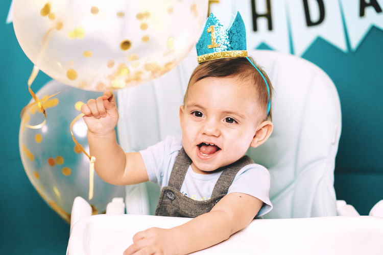 Cute baby boy holding balloon on high chair in birthday party