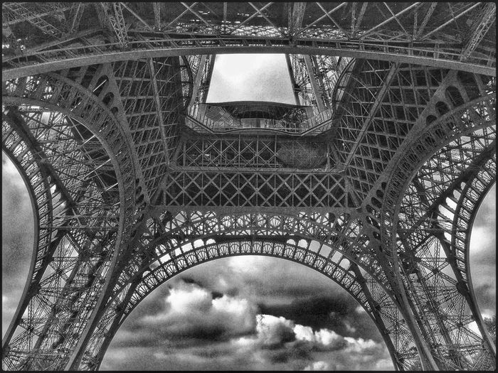 Directly Below Shot Of Eiffel Tower Against Clouds