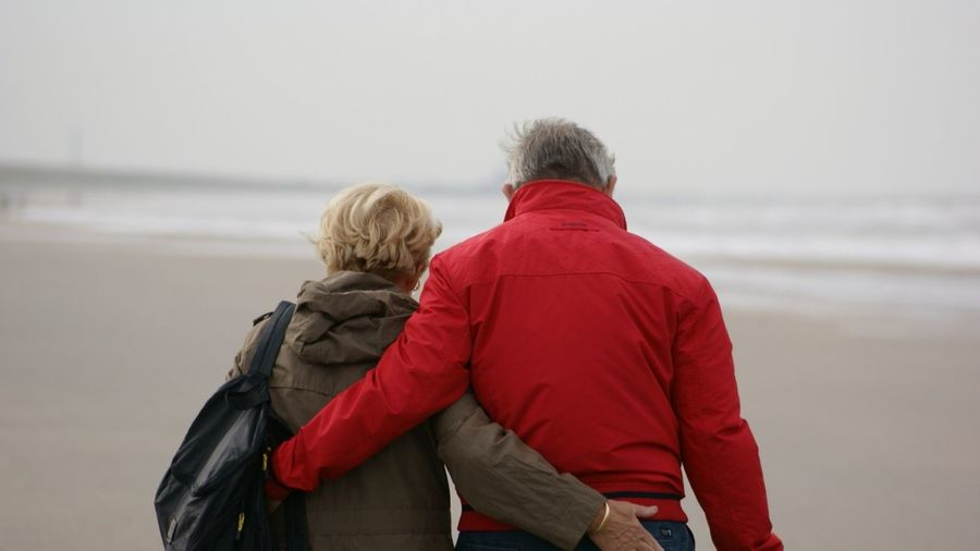 People And Places Rear View Togetherness Men Casual Clothing Love Lifestyles Person Warm Clothing Jacket Bonding Water Heterosexual Couple Focus On Foreground Sea Tourism Winter Coat Day Vacations Non-urban Scene Sky Beach Walk