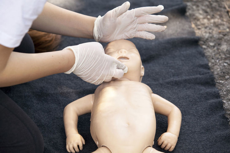 Cropped image of paramedics performing cpr on baby mannequin