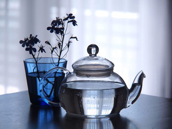 Close-up of teapot by vase on table at home
