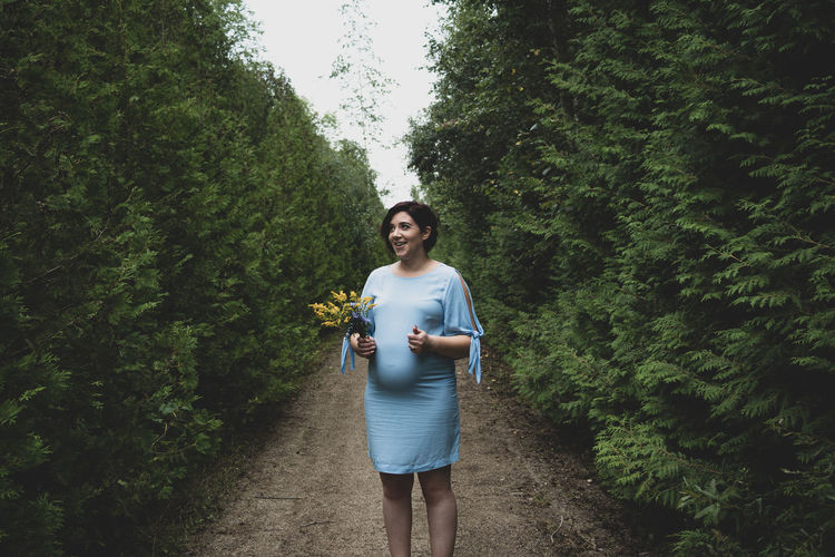 Pregnant Woman Standing On Field Amidst Plants