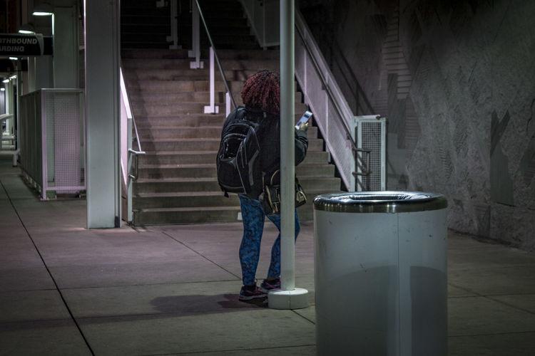 Woman Using Mobile Phone At Subway Station