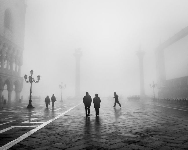 Monochrome image of couples walking through a very foggy St Marks Square, Venice, Italy. Alone Black And White Fog Friendship Incidental People Italy Leisure Activity Lifestyles Light Melancholic Landscapes Men Monochrome Outdoors Real People St Marks Square Time Togetherness Tourism Traveling Vacations Venice Walking Women The Street Photographer - 2016 EyeEm Awards