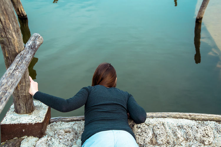 Rear View Of Woman Bending On Surrounding Wall Against Lake