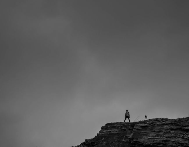 Silhouette people standing on mountain against clear sky