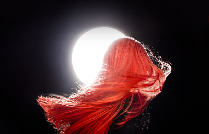 Woman with dyed hair against sky at night