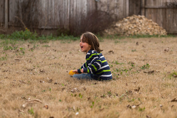 Full length of boy sitting on land outdoors