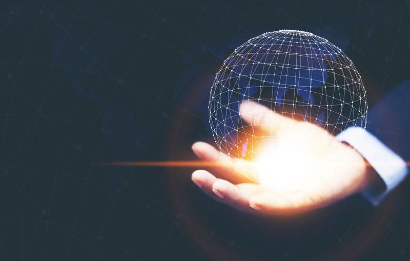 Digital composite image of hand holding globe