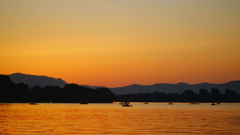 Sunset Mountain Lake Water Landscape Silhouette Tree Outdoors Scenics No People Mountain Range Nature Sky Beauty In Nature Day Silhouette Warm Glow Vacations Yellow Travel Light And Shadow Hangzhou,China West Lake, Hangzhou China View Lake View