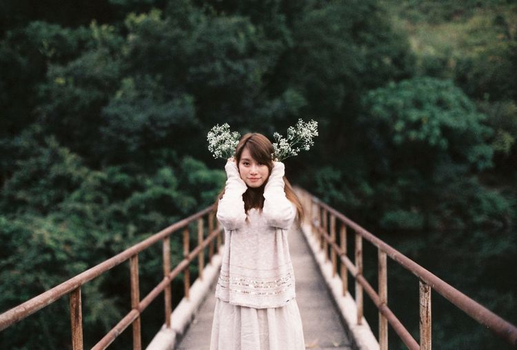 Portrait of a young woman standing on footbridge