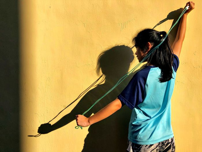 I am champion of rope skipping. Yellow Wall Skipping Rope Rope Skipping Girl Young Adult Real People Two People Lifestyles Wall - Building Feature Three Quarter Length People Men Leisure Activity Standing Waist Up Holding Day Outdoors Rear View Yellow