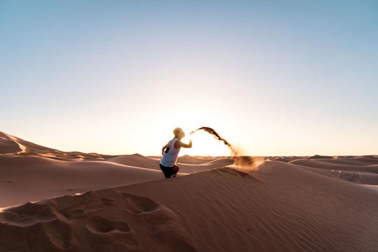 Man blowing sand in desert against sky
