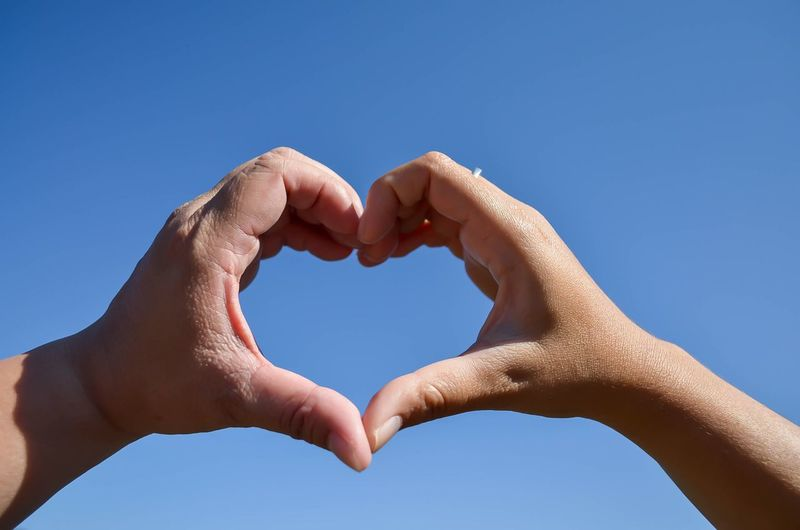 Low angle view of couple making heart shape against clear blue sky