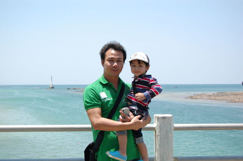Portrait of father carrying son while standing against sea