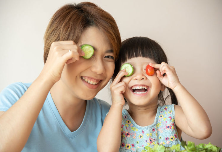 Portrait of smiling mother and daughter holding food over eyes