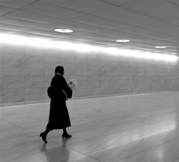 Full length of woman walking in illuminated subway