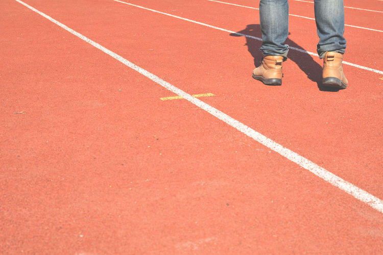 Low section of man standing on sports track