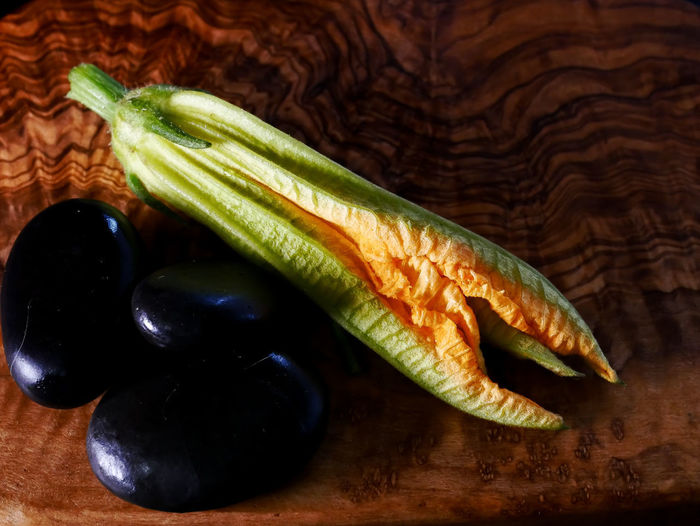 Courgette Flower Black Color Close-up Focus On Foreground Food Food And Drink Freshness Fruit Green Color Group Of Objects Healthy Eating High Angle View Indoors  No People Raw Food Ripe Rocks Still Life Table Vegetable Wellbeing Wood - Material