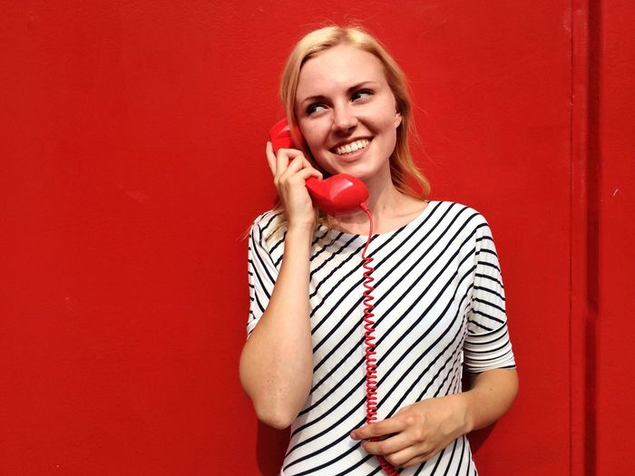 Woman Telephone Telephone Cable Red Telephone Telephone Receiver Old Telephone Vintage Retro Girl Communication Striped Red One Person Blond Hair Portrait Young Adult Standing Looking At Camera Smiling Beautiful Woman Only Women Happiness Young Women Adult One Woman Only Indoors  Real People Adults Only One Young Woman Only