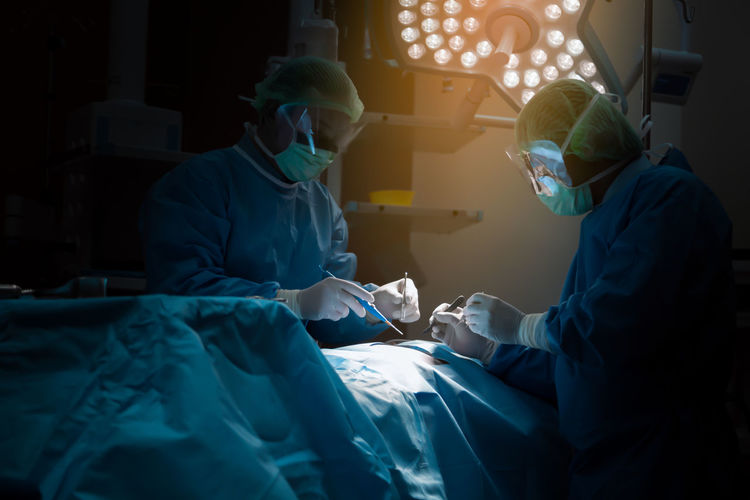 Surgeons operating patient in room