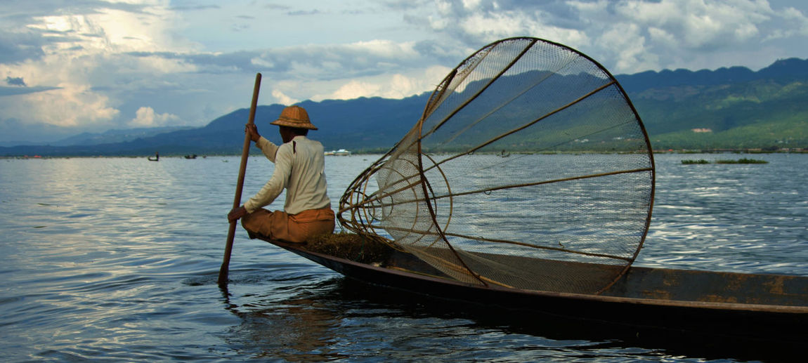 Traditional Clothing Tranquility Boat Burma Burmese Fisherman Fishing Net Inle Lake, Shan State, Myanmar Lifestyles Mode Of Transport Occupation One Person Outdoors Real People Rear View Sky Travel Destinations Water