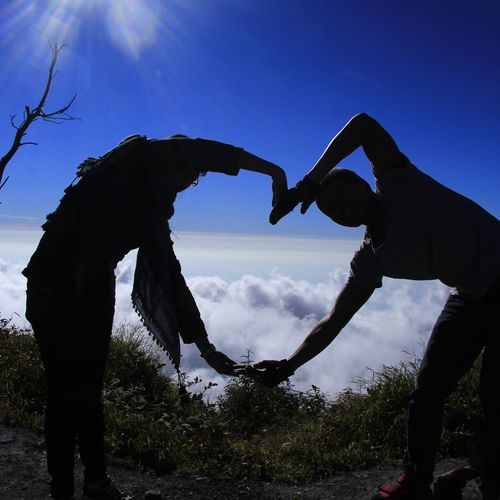 Low angle view of couple kissing against sky
