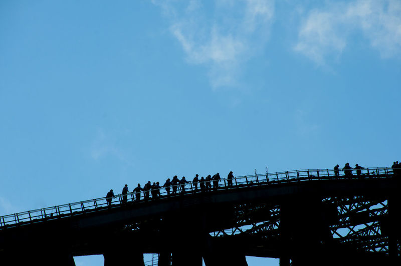 Low angle view of silhouette people on bridge against sky