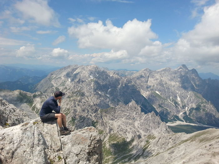 Full length of man sitting on rocks against mountains and sky