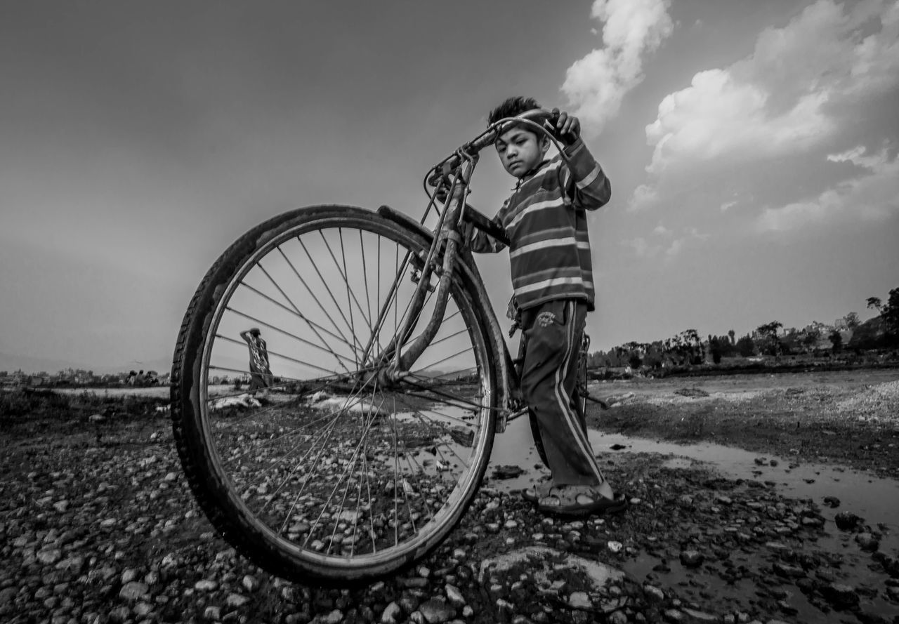 transportation, full length, bicycle, real people, sky, one person, childhood, field, outdoors, standing, day, land vehicle, boys, nature, people