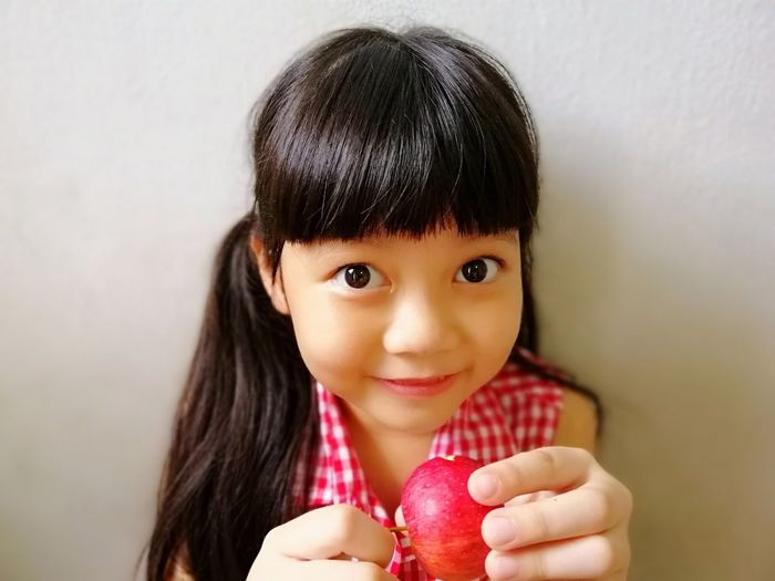 Healthy girl Holding Fringe Hair Daughter Long Hair Relax 6-7 Years Thai Kid Food Fruit Organic Healthy Cute Girl Eating Apple Sweet Fruits Adorable Girl Asian Girl Human Hand Portrait Child Smiling Childhood Looking At Camera Red Happiness Pretty Hungry Eye Color