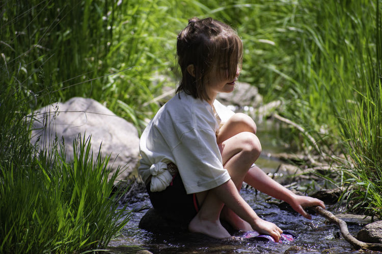 Side view of girl holding fabric while crouching amidst stream
